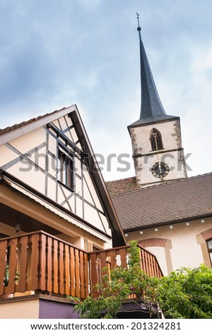 Timber frame house and church, Mittelbergheim, Alsace, France - stock photo