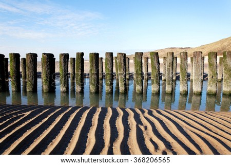 timber groyne with reflexion in water on a beach with sand lines - stock photo