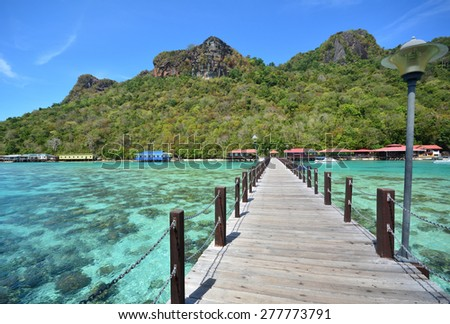 Timber jetty headding towards the Bohey Dulang Island, Tun Sakaran Marine Park in Semporna, Sabah Borneo, Malaysia. Clear green water with a blue sky. - stock photo