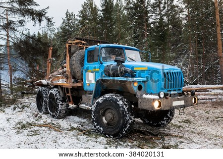 Timber truck loading in forest. winter - stock photo