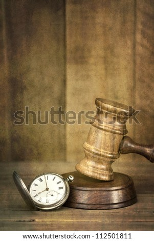 Time and justice concept.  Old pocket watch with wooden gavel, with timber background.  Added grunge effects. - stock photo
