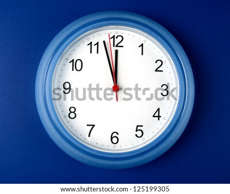 Time - Clock about to hit midnight or noon on blue background - stock photo