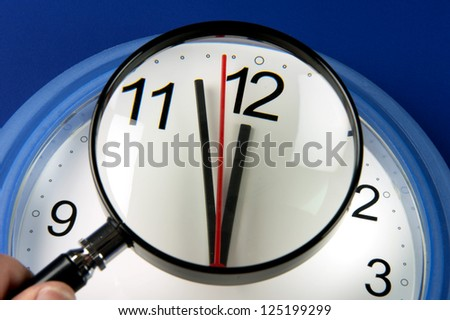 Time - Closeup clock hands about to hit midnight or noon  through magnifying glass - stock photo