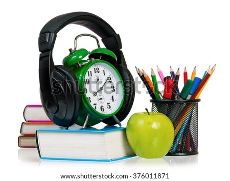 Time concept - alarm clock with books, headphones, pencils and apple - stock photo