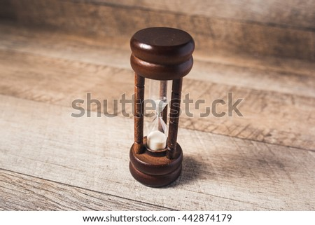 Time concept. closeup sandglass on wood background