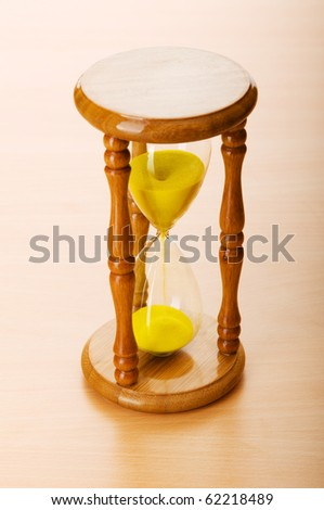 Time concept - hourglass against the wooden background
