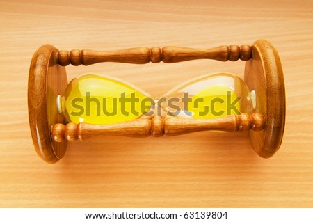 Time concept - hourglass against the wooden background - stock photo