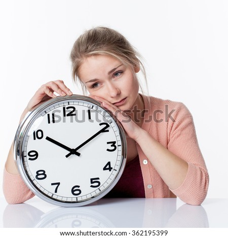 time concept - sad beautiful young blond woman leaning on a clock, showing depressing nostalgia of adolescence, white background