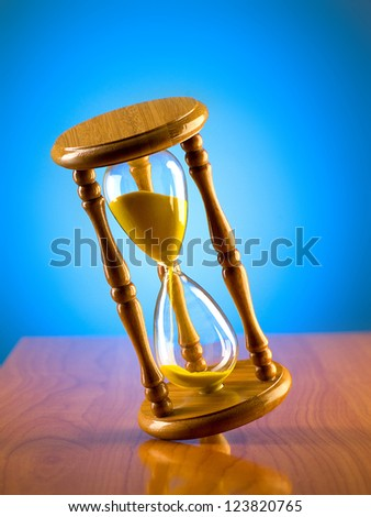 Time concept with hourglass against background - stock photo