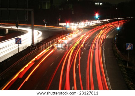 Time exposure photo (30 seconds) with a street at night and automobile headlights of a multiple lane city street and a traffic light, seen in Kassel, Germany