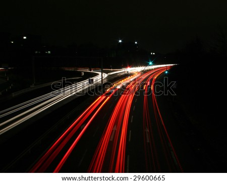 Time exposure photo (30 seconds) with a street at night and automobile headlights of a multiple lane city street and a traffic light, seen at the Autobahn near Auestadion in Kassel, Germany - stock photo
