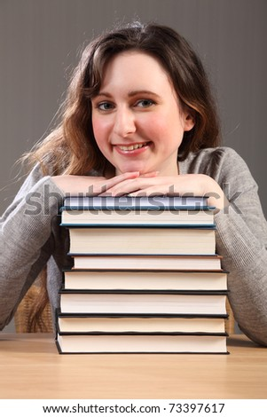 Time for a break for young caucasian student girl, sitting with big smile resting chin on stack of work books. - stock photo