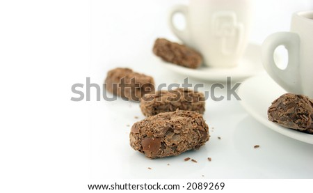 Time for a break - two Coffee cups on a white background with chocolates