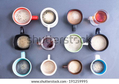 Time for a coffee break for office with a neat line up of different mugs handles looking different directions, freshly brewed foamy coffee and teas for a daily dose of caffeine to energize your day - stock photo
