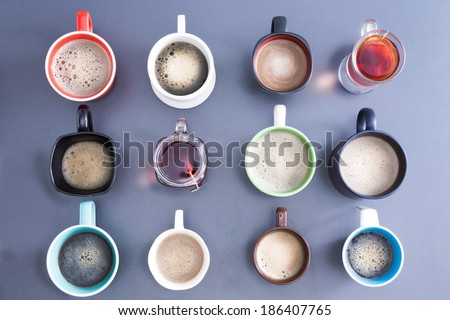 Time for a coffee break or teatime with a neat line up of different mugs and glasses containing freshly brewed coffee and tea for a daily dose of caffeine to energize your day, view from above - stock photo