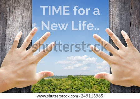 Time for a New life word floating on the sky behind 2 hands trying to open a wooden door. - stock photo