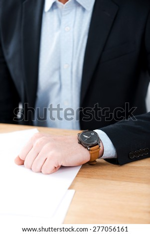 Time for business. Close-up of businessman wearing watch on his hand while sitting at his working place - stock photo