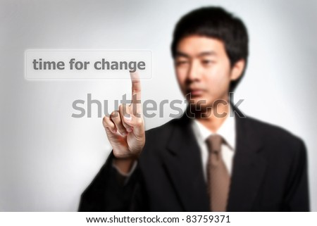 time for change. Asian business man pressing a touchscreen button - stock photo