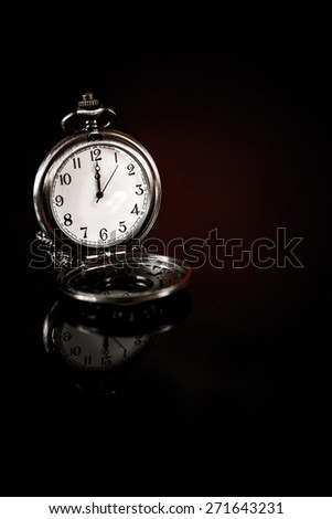 time for change, to do things NOW concept - pocket watch over a black background - stock photo
