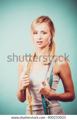 Time for diet slimming weight loss. Health care and healthy lifestyle. Young fitness woman fit girl with many colorful measure tapes on blue - stock photo