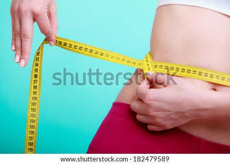 Time for diet slimming weight loss. Health care and healthy nutrition. Young fitness woman fit girl with measure tape measuring her waistline on blue green - stock photo
