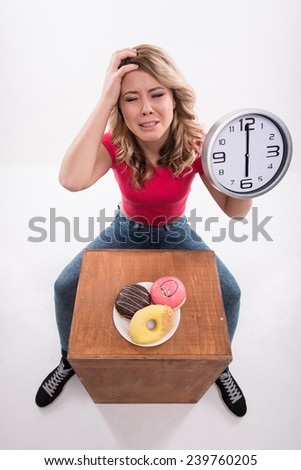 Time for diet slimming. Young beautiful woman with clock keeps from eating doughnuts after 6 pm - weight loss concept, top view isolated on a white background - stock photo