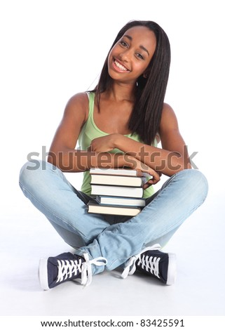 Time for education from pretty young African American teenager school girl student with big beautiful smile, sitting cross legged on floor wearing blue jeans and vest holding school books. - stock photo