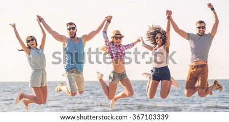 Time for fun. Group of happy young people holding hands and jumping with sea in the background