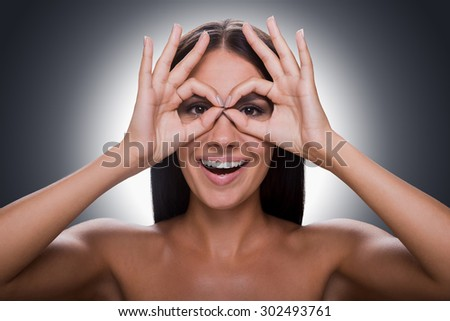 Time for fun. Portrait of cheerful young shirtless woman looking at camera through fingers while standing against grey background - stock photo