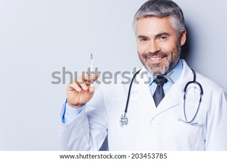 Time for injection! Confident mature doctor holding syringe and smiling while standing against grey background - stock photo