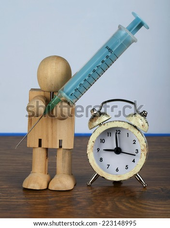 Time for medication conception with wooden man and syringe - stock photo