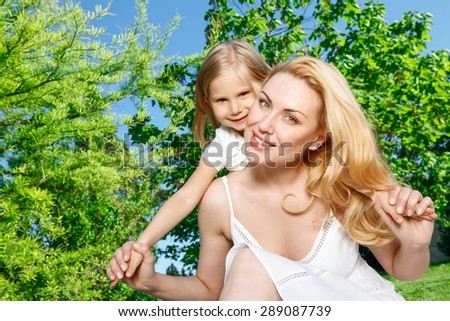 Time for playing. Young pretty mommy holding her little daughter behind her back during picnic.  - stock photo
