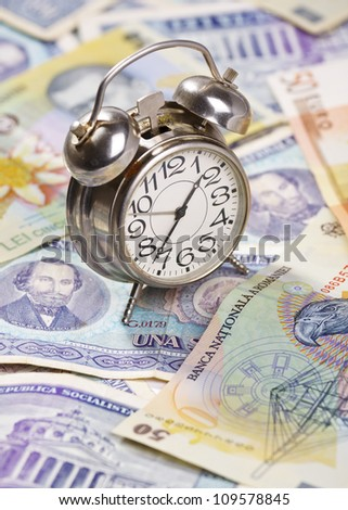 Time for profit. Old alarm clock on stack of euro and romanian banknotes, very old and new ones. - stock photo