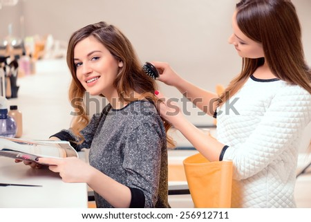 Time for something new. Side view of a young beautiful woman discussing hairstyling with her hairdresser while sitting in the hair salon and getting her hair done  - stock photo