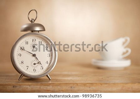 time for tea, retro alarm clock and tea cups, hessian burlap background with uneven light - stock photo