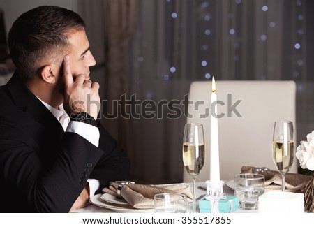 Time gifts. Elegant Man sitting near the table. Party, drinks, holidays, luxury and celebration concept. (focus on hands)