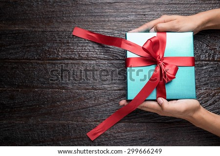 Time gifts - gift box in hand girls on wood table - stock photo