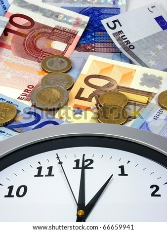 Time is money. A clock lying on a background of euro currency. - stock photo