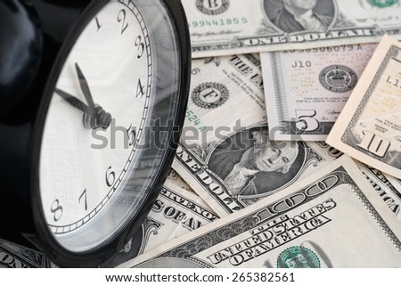 Time is money. Alarm clock and dollar banknotes. - stock photo