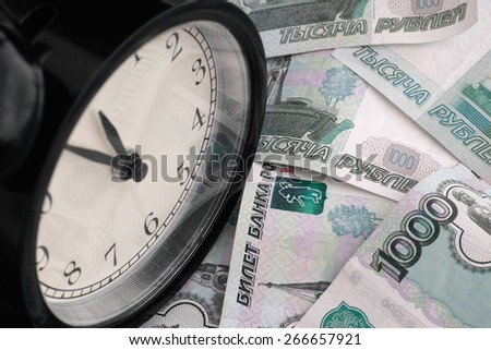 Time is money. Alarm clock and russian money. - stock photo