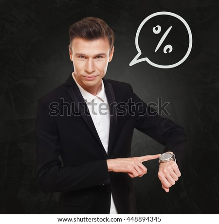 Time is money. Businessman point at his watch showing banking concept. Man in suit with watch at black background, thinking cloud with percent, interest rate sign. Financial business, bank deposit - stock photo