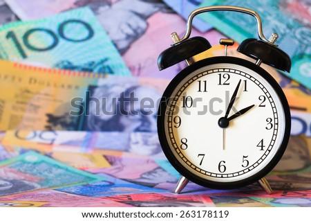Time is money, clocks under australian dollars - stock photo