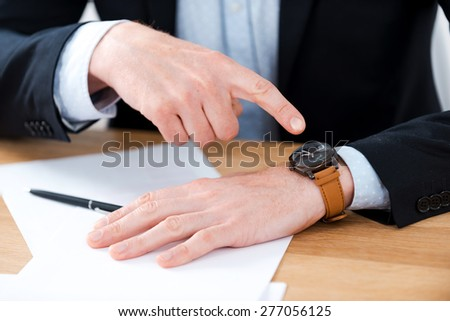 Time is money. Close-up of businessman pointing on his watch while sitting at his working place - stock photo