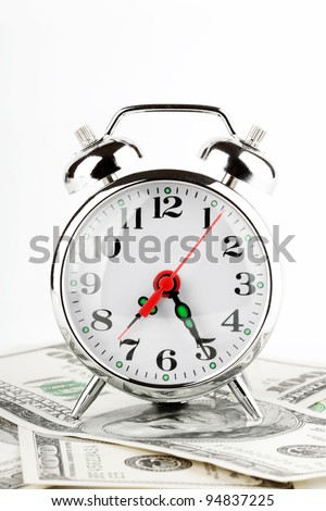 Time is money concept. Retro styled alarm clock on the money. - stock photo