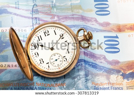 Time is money concept with hundred swiss franc bills and golden pocket watch. - stock photo