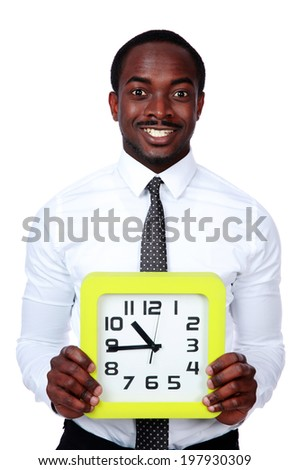 Time is money! Handsome african man holding a clock over white background - stock photo