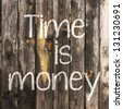 Time is money handwritten with white chalk on wooden background - stock photo