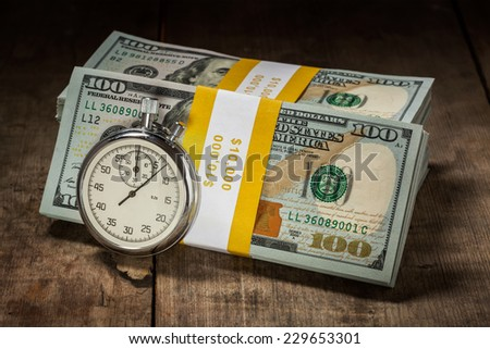 Time is money loan concept background - stopwatch and stack of new 100 US dollars 2013 edition banknotes (bills) bundles on wooden background - stock photo