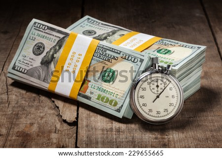 Time is money loan debt deadline concept background - stopwatch and stack of new 100 US dollars 2013 edition banknotes (bills) bundles on wooden background - stock photo