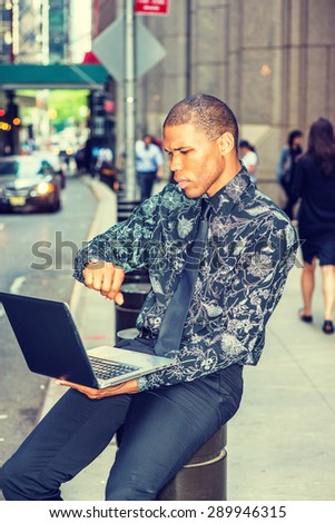 Time is Money. Road to Success. African American businessman working on laptop computer on street in New York, looking at wristwatch, waiting to meet you. Car, people on background. Instagram effect.  - stock photo